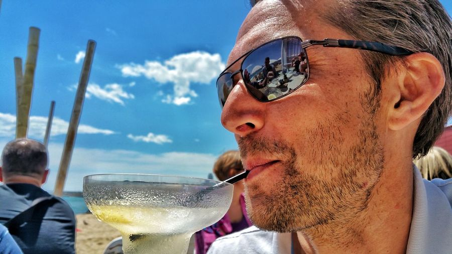 Close-up of man having drink on sunny day