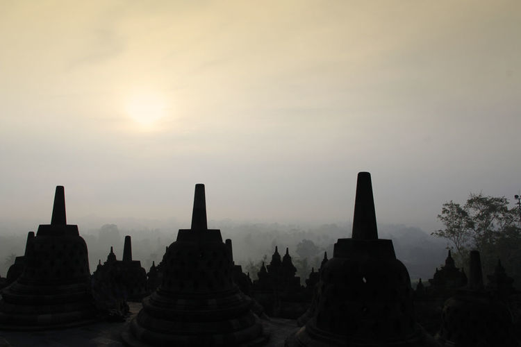 Silhouette Borobudur Temple with the mysteries forest surrounding during sunrise, Yogyakarta, Indonesia Ancient Borobudur Temple Java Yogyakarta Ancient Ancient Civilization Architecture Architecture And Art Buddhism Built Structure Dawn Fog Forest History Mount Merapi Nature No People Outdoors Place Of Worship Religion Religious Architecture Sky Stone Material Sunrise Sunset