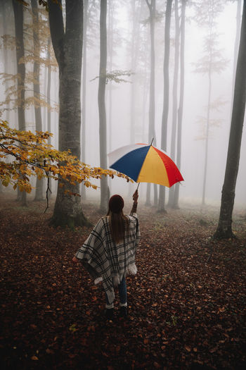 Woman standing with umbrella during autumn