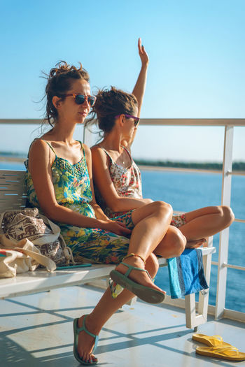 Young women spending leisure time on boat deck against sky