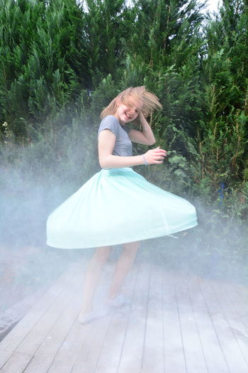 Girl dancing amidst dust on floorboard in back yard
