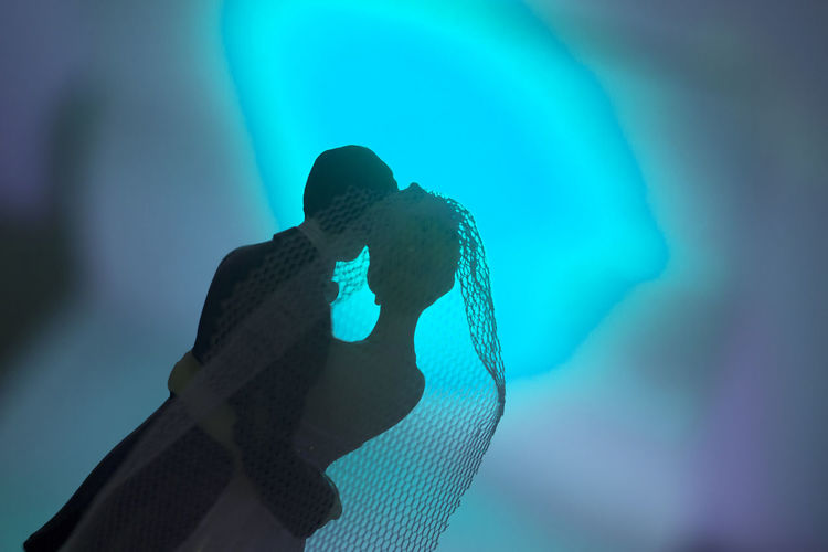 Low angle view of man holding hands against blue background