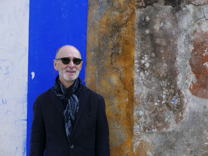 Senior Man Wearing Sunglasses While Standing Against Weathered Wall