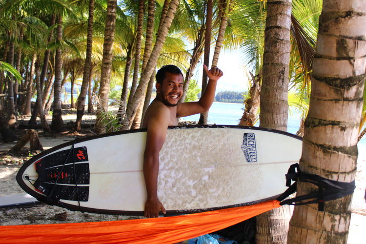 Portrait of smiling man holding surfboard at beach