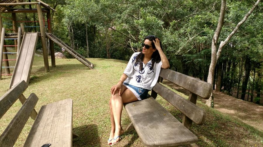 Young woman relaxing on wooden bench against trees at park