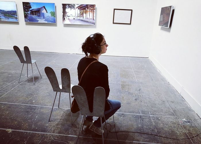 """Tutto Il Tempo Che Ci Serve"" Woman Portrait Chairs In Front Of Paintings Modern Full Length Woman Sitting In A Museum in Biennale Architettura a Venezia 2016"