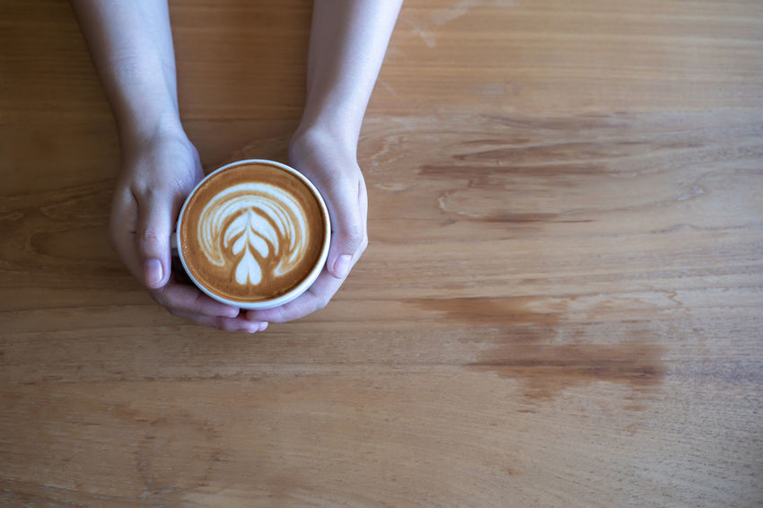 Indoors  Coffee Cup One Person Coffee Froth Art Frothy Drink Coffee - Drink Wood - Material Food And Drink Drink Table Hardwood Floor Wood Cappuccino Refreshment Mug Directly Above Cup Human Body Part Food Hot Drink Flooring Latte Hand