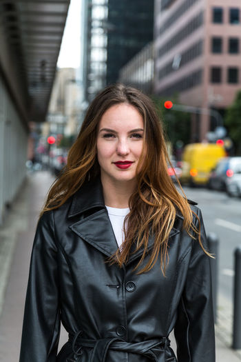 Portrait of beautiful woman wearing black jacket standing in city