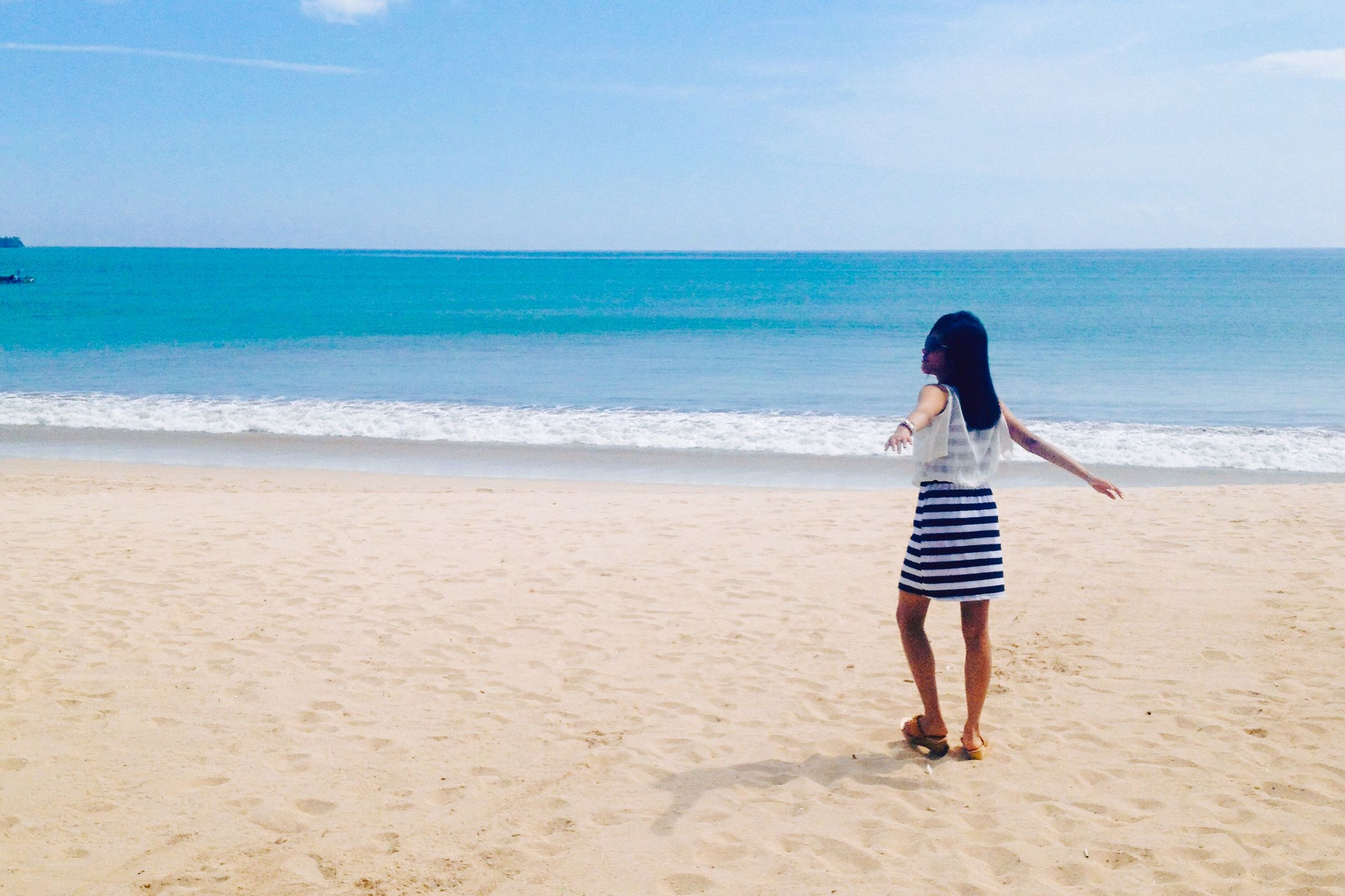 sea, beach, horizon over water, shore, water, sand, full length, lifestyles, leisure activity, casual clothing, sky, vacations, rear view, childhood, beauty in nature, person, standing, scenics