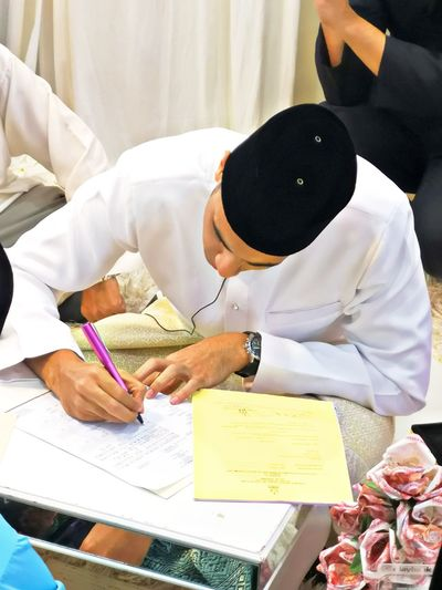 Man in traditional clothing signing in document at home