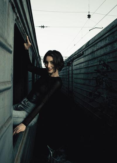 Portrait of woman sitting on train window