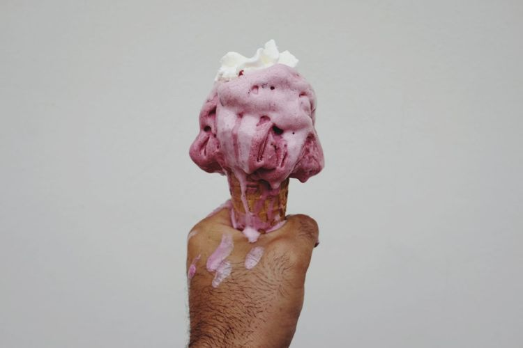 Cropped hand of man holding ice cream cone against white background
