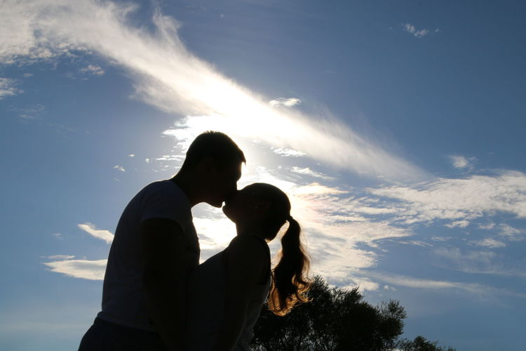 Low angle view of man and woman kissing against sky on sunny day
