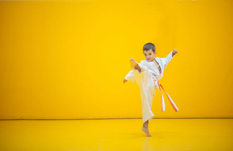 karate kid practicing kick on yellow background. Full Length One Person Studio Shot Indoors  Human Arm Colored Background Yellow Young Adult Standing Adult Dancing Limb Women Yellow Background Arms Raised Wall - Building Feature Lifestyles Clothing Stage Human Limb Karate Kyokushin