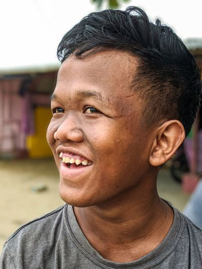 Close-up of smiling boy looking away outdoors