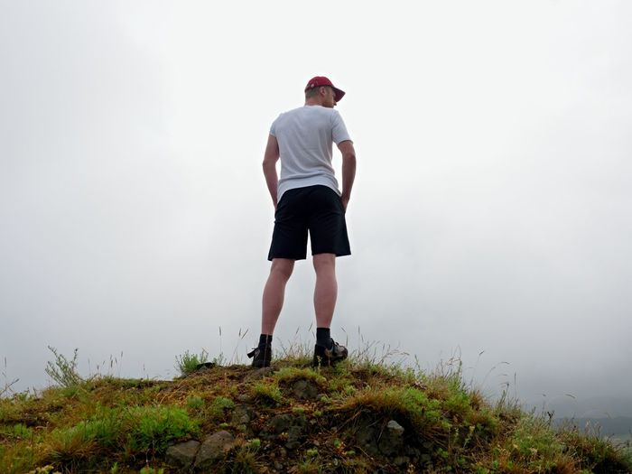 Man in cloud of fog. hiker in white black sportswear and red cap stand on rocky peak . around mist