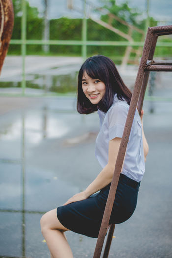 Portrait of smiling young woman sitting on metallic outdoor play equipment at playground during rainy season