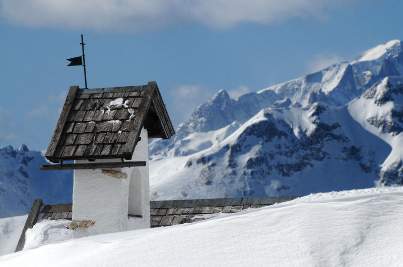 Building on snowcapped mountain against sky