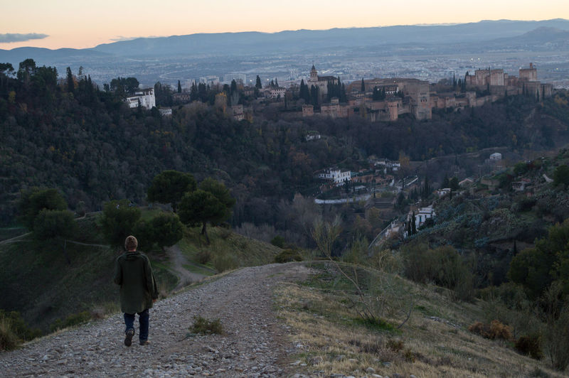 Granada, Spain SPAIN Andalusia Sacromonte Alhambra Albaycin Albaicin Building Exterior Architecture Built Structure City Mountain One Person Nature Standing Plant Rear View Tree Leisure Activity Residential District Building Sky Real People Cityscape Full Length Outdoors
