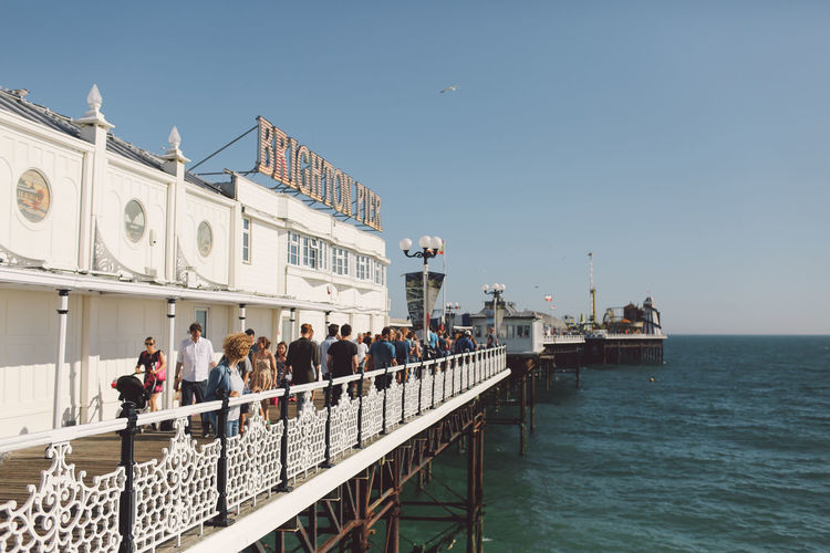People On Palace Pier Over Sea Against Clear Sky
