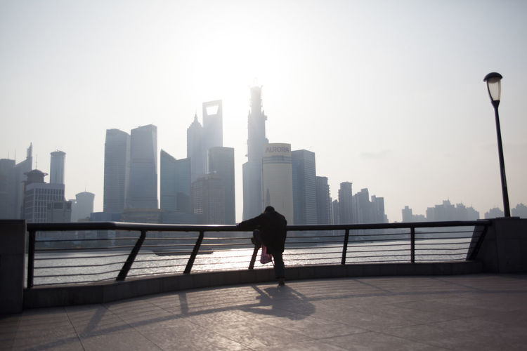 Rear View Of Man Standing By Railing In Front Of Huangpu River And Cityscape