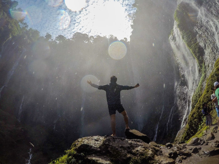 Full Length Of Male Hiker With Arms Outstretched Standing Against Waterfall