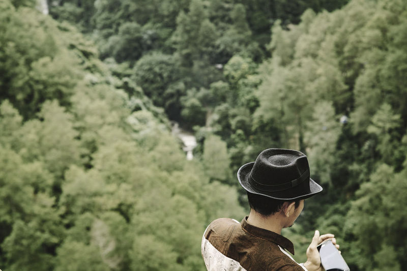 High angle view of man wearing hat while holding mobile phone on mountain against trees
