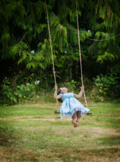 Pure Joy. Summer brings out the best in all of us. Dress Fun Green Color Joyful Plant Playing Games Summertime Swinging Child Childhood Day Full Length Fun Grass Joy Nature One Girl Only One Person Outdoors People Playing Pretty Summer Swing Tree