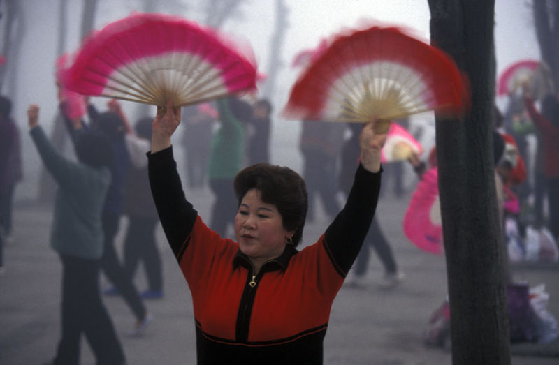 Mid adult woman holding hand fan while performing at park