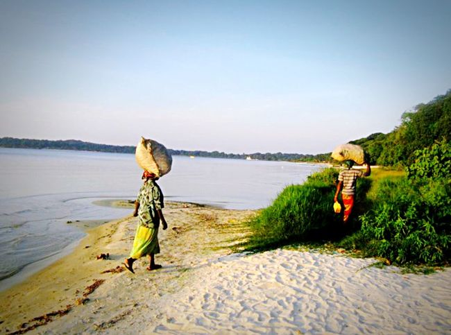 Edge Of The World Sesse islands, Uganda. Two women taking supplies home from a long journey. These islands are 80% AIDS infected due to fishermen and lack of education. Uganda