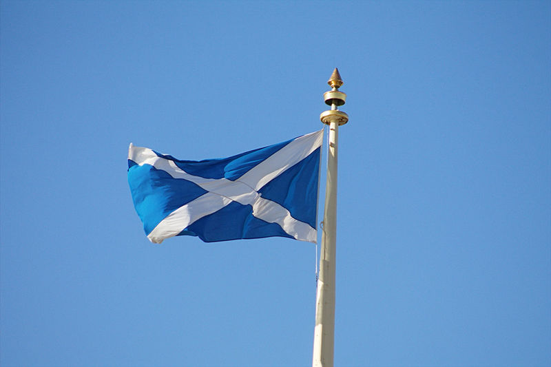 Low angle view of flag pole against clear blue sky
