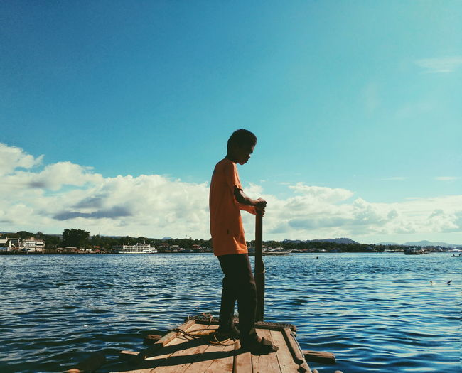 Boy standing by sea against sky