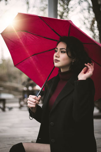Young woman with umbrella standing in rain