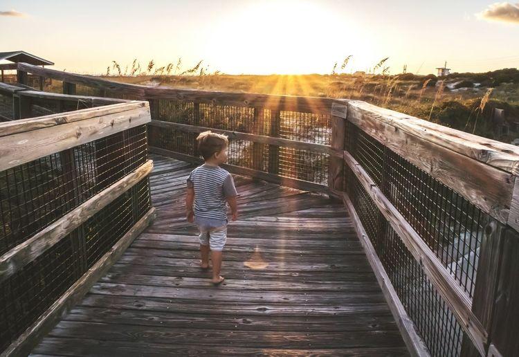 Rear view of boy standing on footbridge