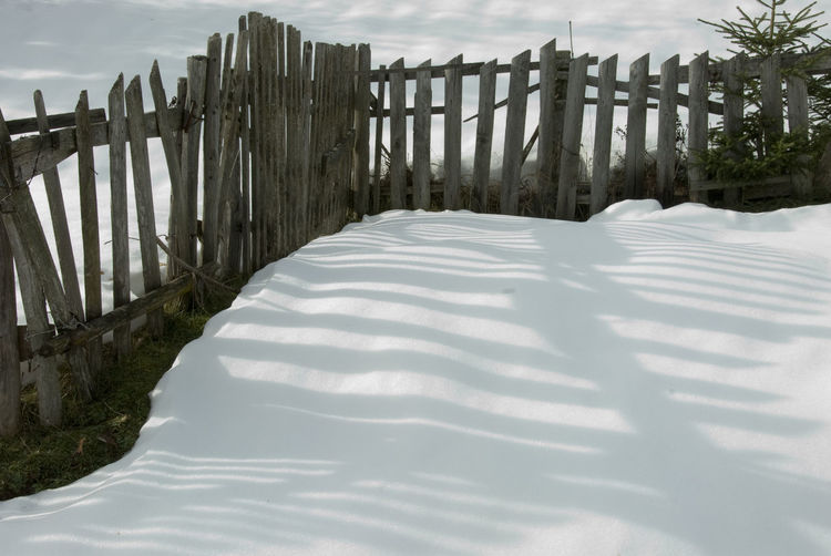 Wooden fence on snow covered land against sky