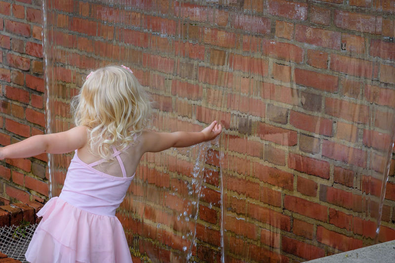 Little girl reaching into water fountain in summer Back View Reaching Education Outdoors Ballerina Playing Summer Pink Beautiful Carefree Blond Hair Youth Kid Feature Fountain Waterfall Experience Nature Childhood Unplugged Water Hand Little Child Touch