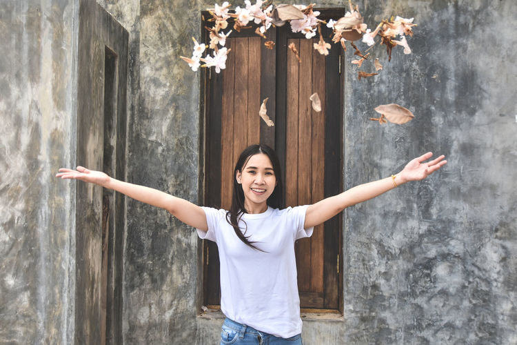 Portrait of smiling young woman throwing leaves while standing against wall