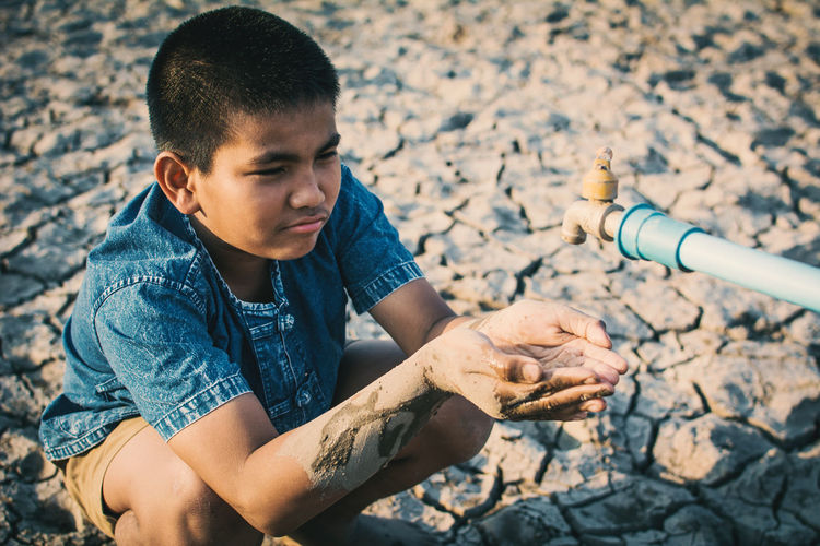 Close-up of boy cupping hands below faucet on cracked field