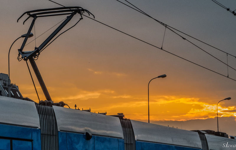 Colour Your Horizn Tram Cable Low Angle View Mode Of Transport Outdoors Sky Street Light Sunset Transportation Wires Wires And Sky