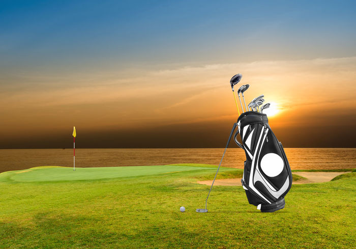 Golf equipment and golf bag ,putter ,ball on green Green Bag Ball Beauty In Nature Comcept Day Flag Golf Golf Course Grass Green - Golf Course Nature No People Outdoors Pole Putter Scenics Sea Sky Sport Sunset Tranquil Scene Tranquility Tree