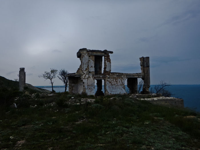 Old castle by sea against sky