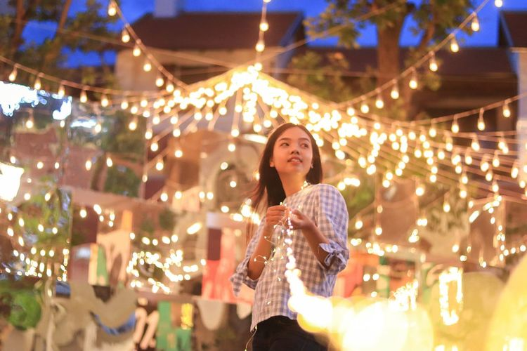 Young woman standing against illuminated lights at night