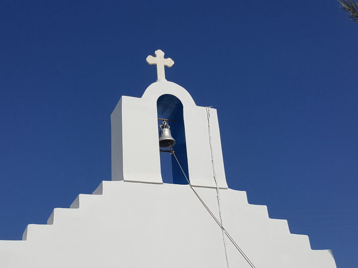 Low angle view of bell tower of church against clear blue sky at santorini