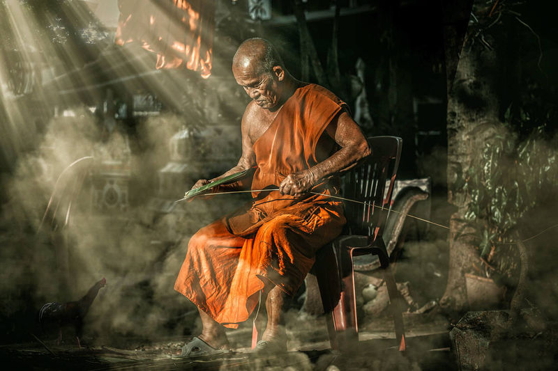 Monk holding thread while sitting on chair at temple