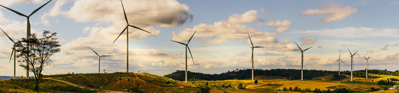 Panoramic view of wind turbine on field against sky