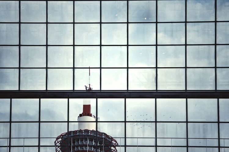 Low Angle View Of Kyoto Tower Seen Through Modern Glass Building