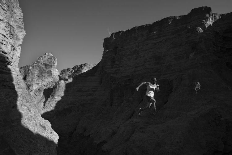 Low angle view of men walking on rocks