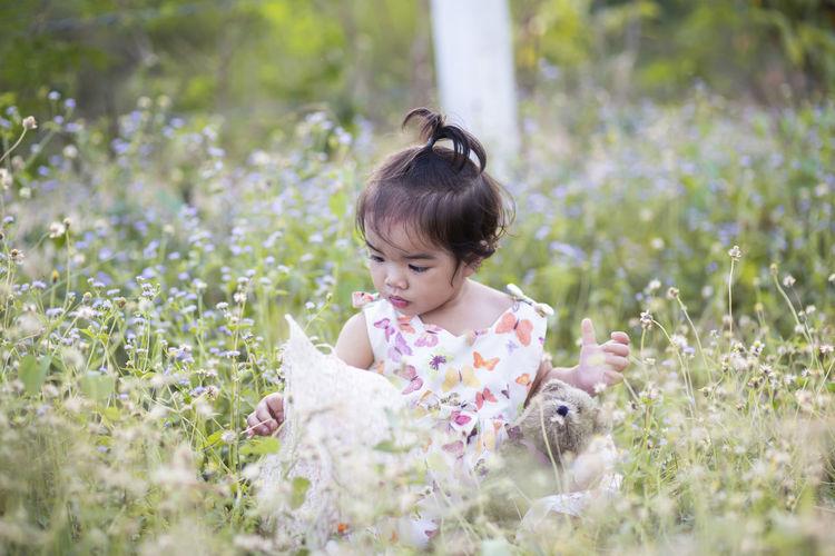 Girl looking at flowering plants on field