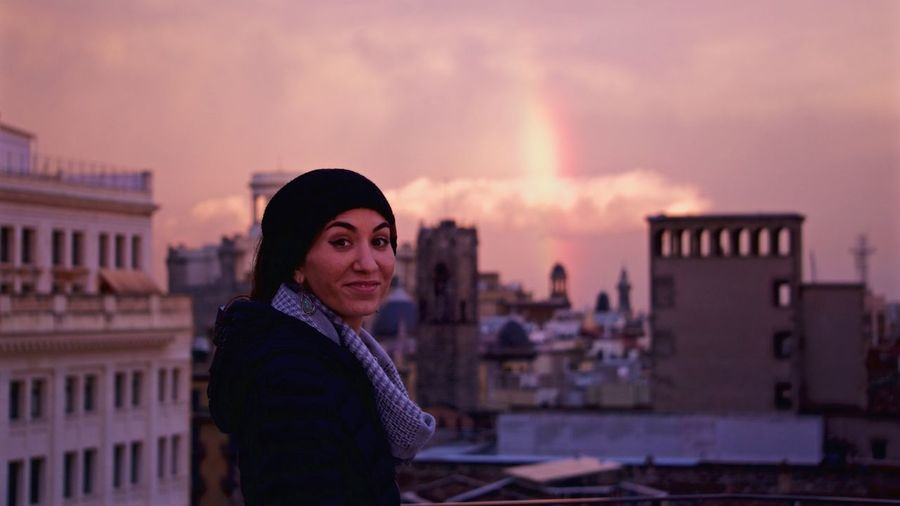 Portrait of young woman standing against cityscape during sunset