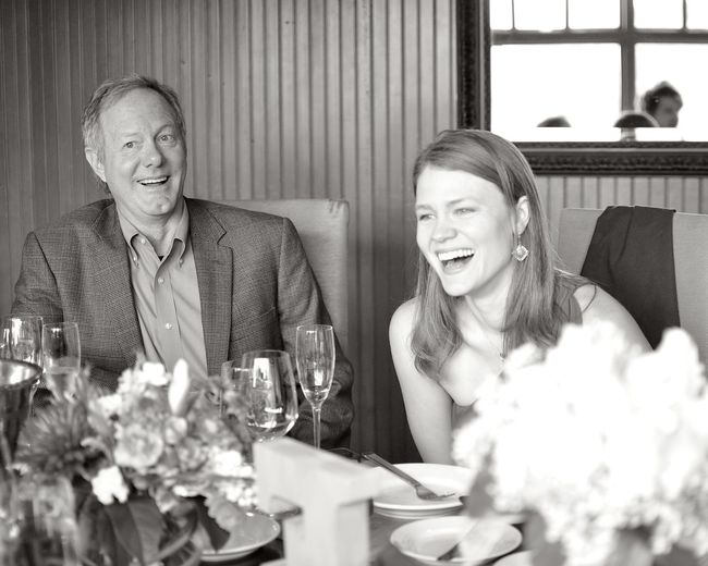 Happy business colleagues sitting on table at restaurant
